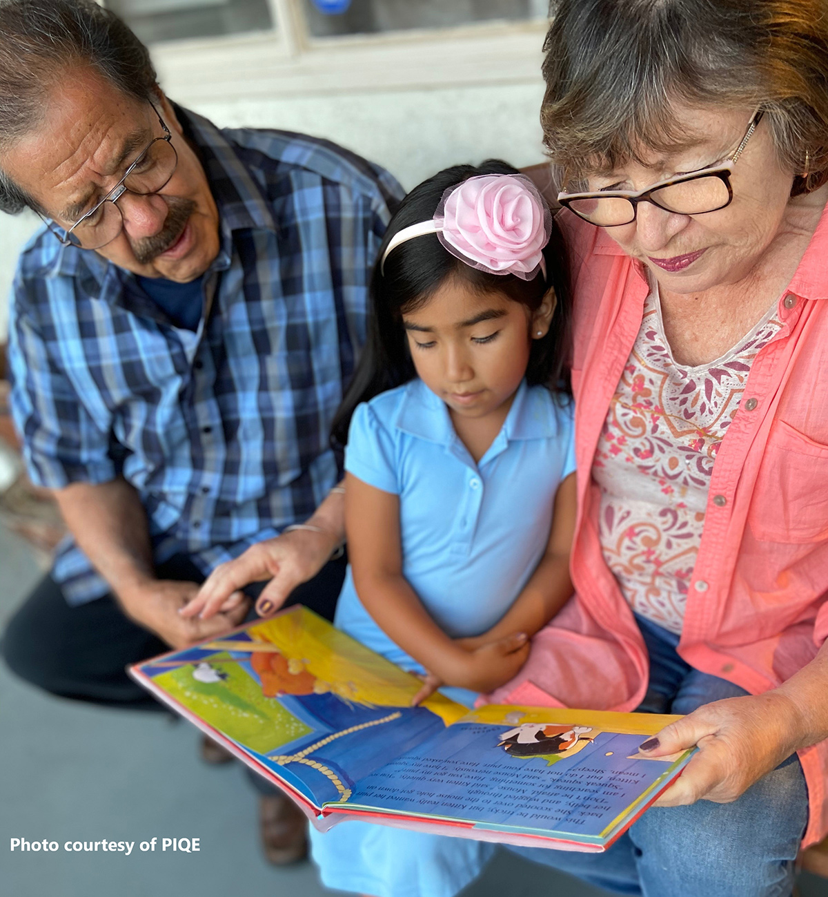 Grandparents reading with their grandchild